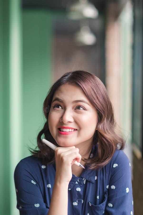 Asiatyong kvinna i kafét nära fönstret, tänka och writien royaltyfri fotografi