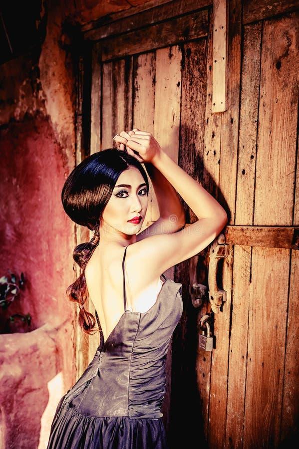 Asien elegant kvinna i svart lång klänning på den wood dörren royaltyfri fotografi