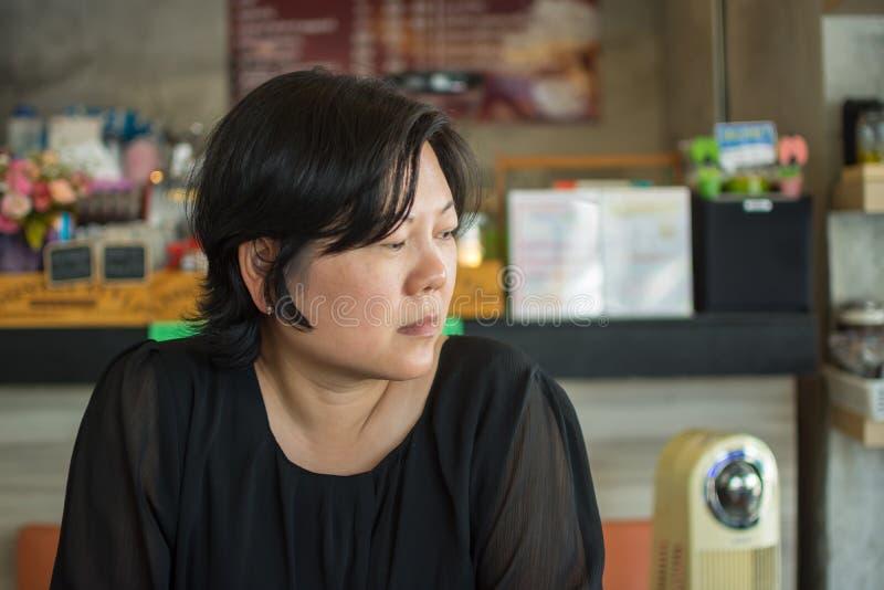 Asien-Frauen denken in der Kaffeestube stockbild