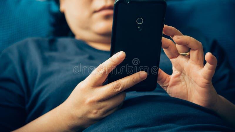 Asien-Frauen 40s, die den Smartphone denkt auf Sofa halten lizenzfreies stockbild