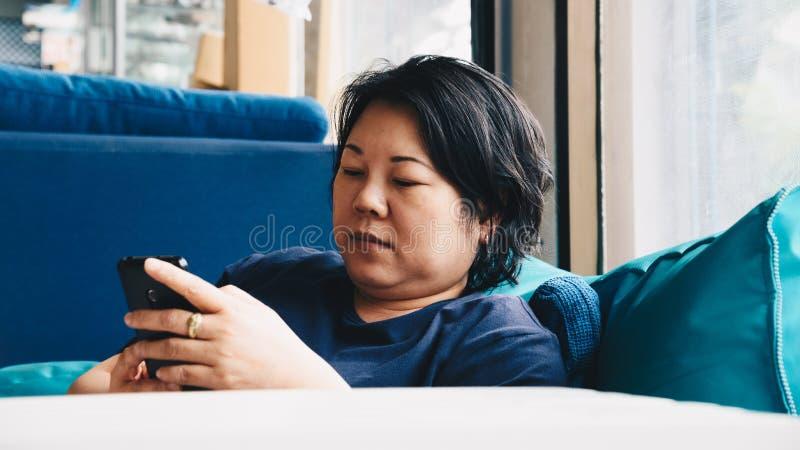 Asien-Frauen 40s, die den Smartphone denkt auf Sofa halten stockbilder