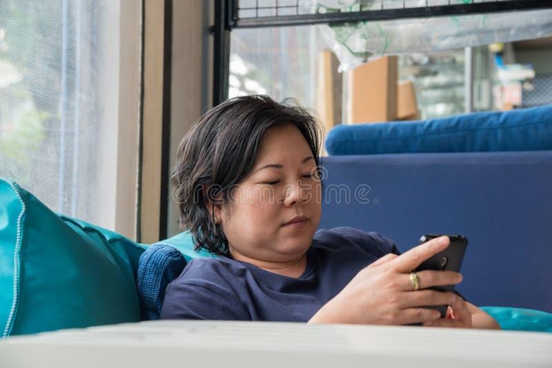 Asien-Frauen 40s, die den Smartphone denkt auf Sofa halten lizenzfreies stockfoto