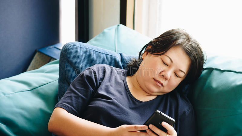 Asien-Frauen 40s, die den Smartphone denkt auf Sofa halten lizenzfreie stockfotografie
