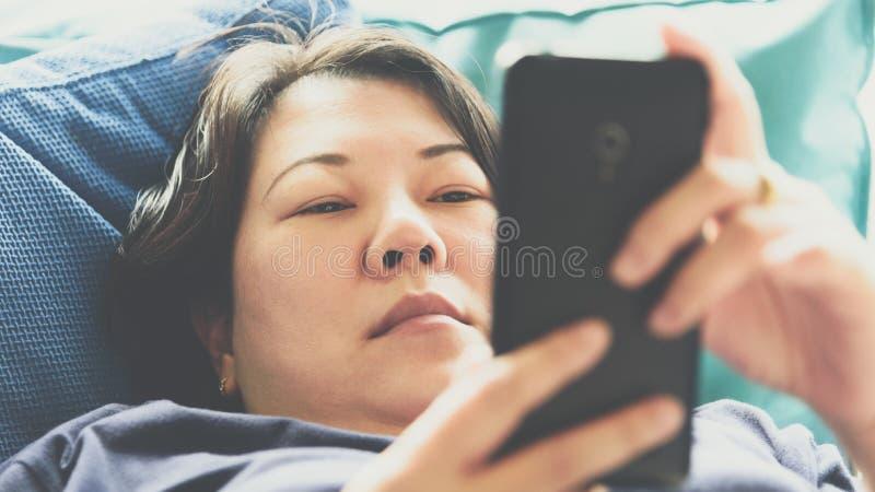 Asien-Frauen 40s, die den Smartphone denkt auf Sofa halten stockfoto