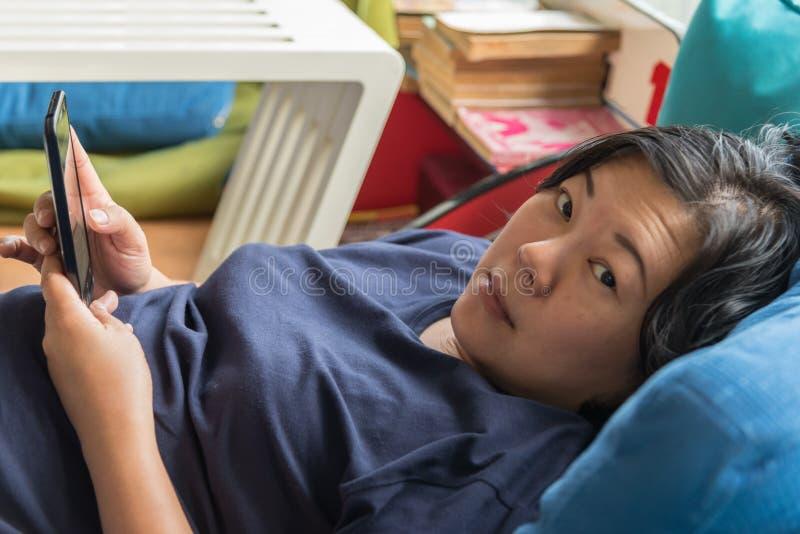 Asien-Frauen 40s, die den Smartphone denkt auf Sofa halten lizenzfreie stockfotos