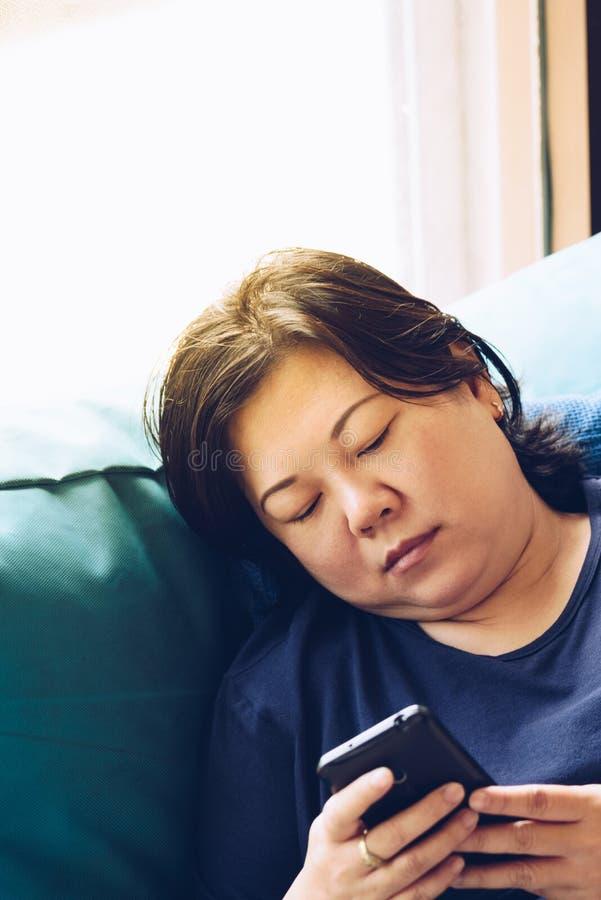 Asien-Frauen 40s, die den Smartphone denkt auf Sofa halten stockfotografie