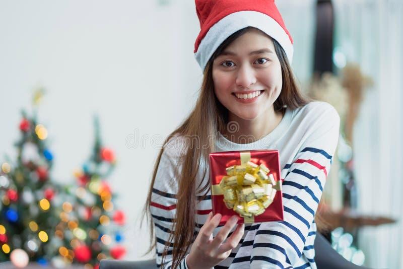 Asien-Frauenlächeln, das Goldweihnachtsgeschenkbox am Urlaubspartyesprit hält stockbild