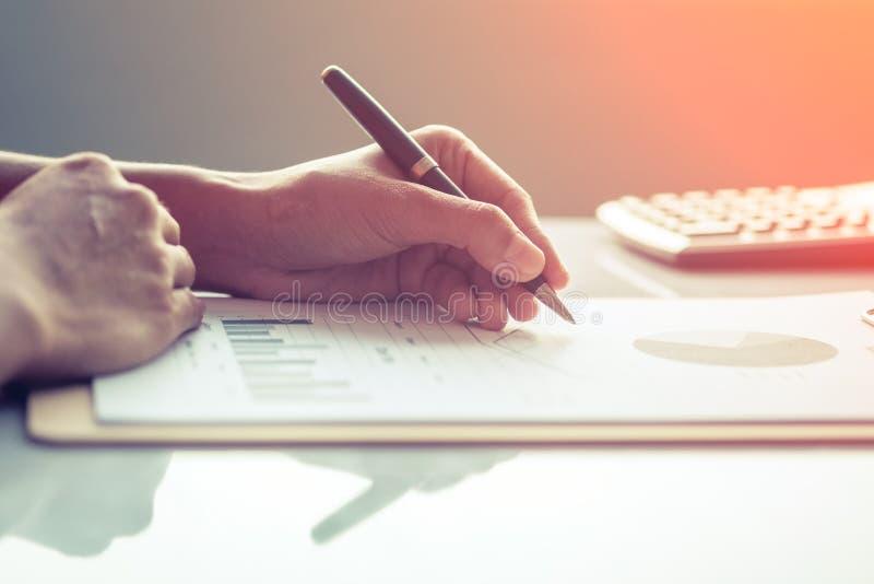 Asien-Geschäftsfrau, die Investitionsdiagramme auf Schreibtisch analysiert stockfotografie