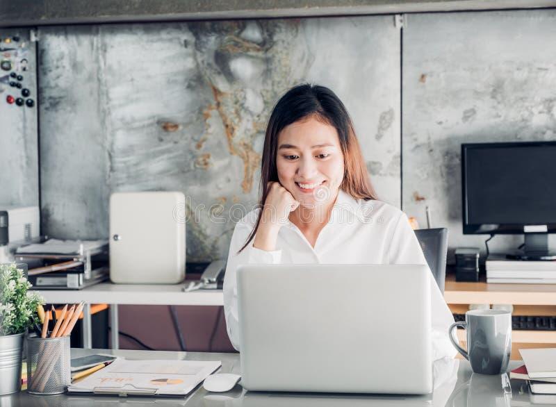 Asien-Geschäftsfrau, die Laptop-Computer und lächelndes Gesicht a betrachtet stockfotografie