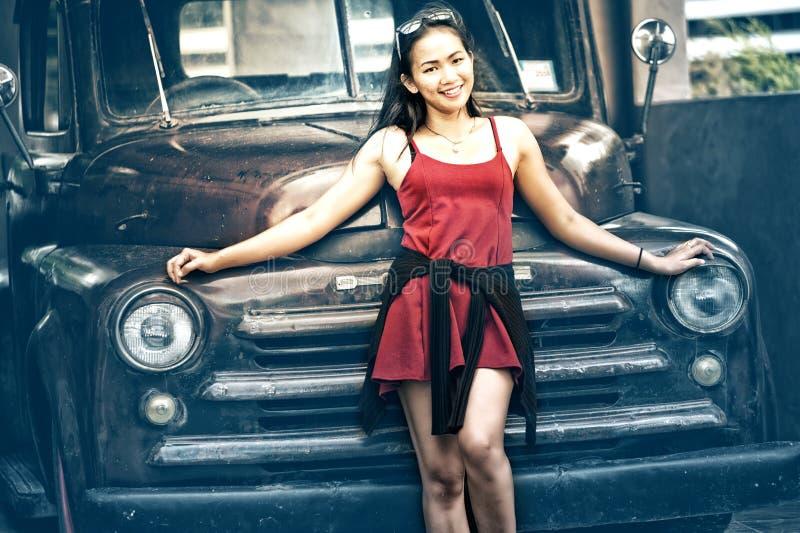 Asien härlig dam som står nära den retro bilen fotografering för bildbyråer