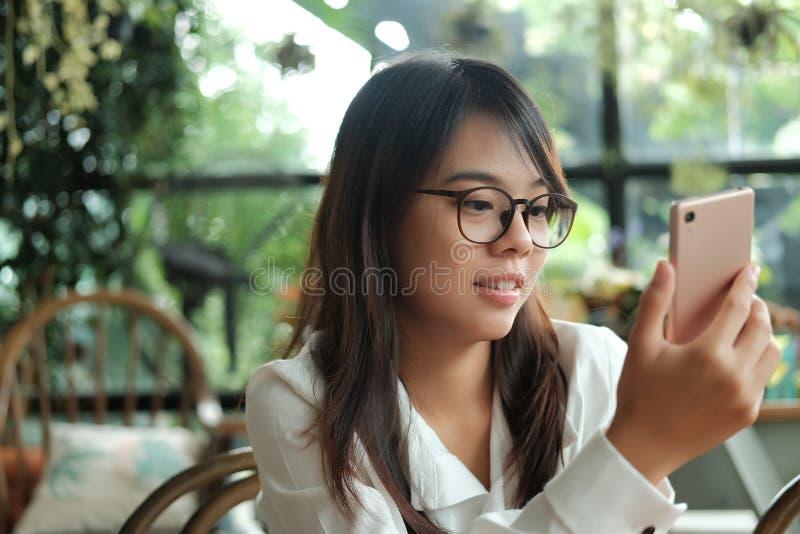 Asien kvinna som använder mobiltelefonen med den främre kameran för selfie och s royaltyfri foto