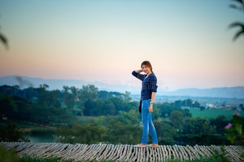 Asien kvinna som poserar på siktspunkt med mountrain fotografering för bildbyråer