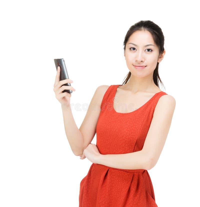 Asien kvinna som spela golfboll i hål mobilen arkivfoton