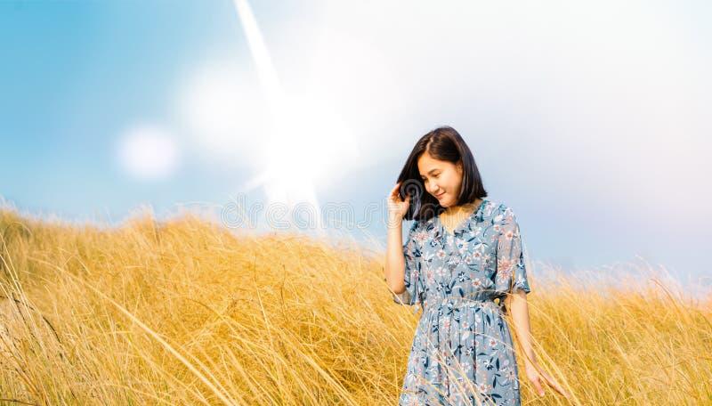 Asien-Mädchen, das draußen Natur genießt Mädchen im blauen Kleid gehend auf das Frühlings-Feld, Sun-Licht lizenzfreies stockfoto