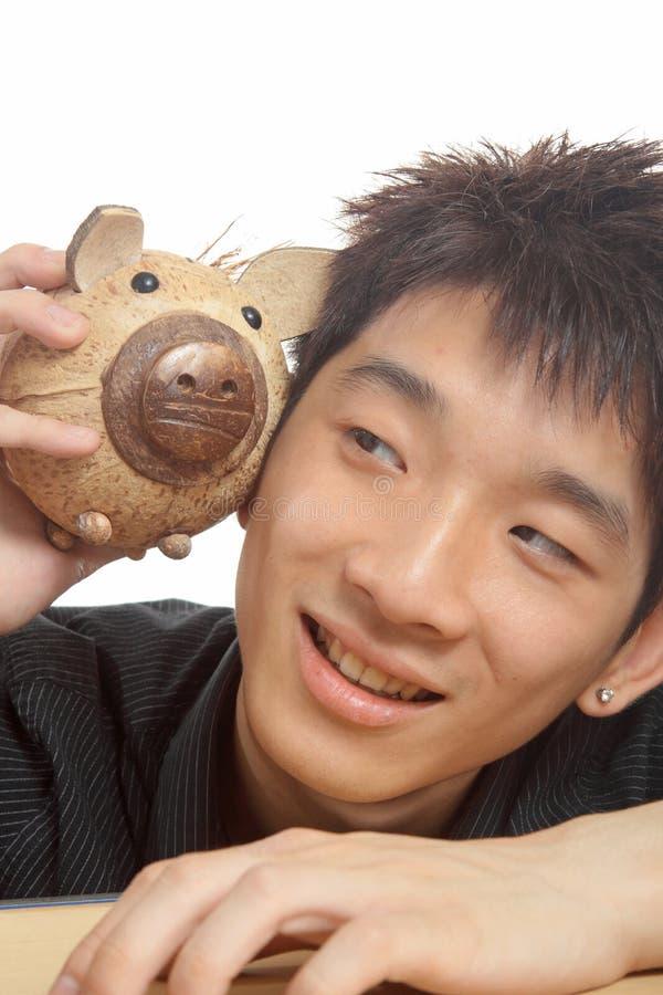 Asien man med den piggy gruppen royaltyfri fotografi