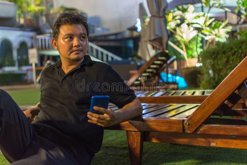 Asien-Mann denken mit Smartphone am Poolside lizenzfreie stockfotos