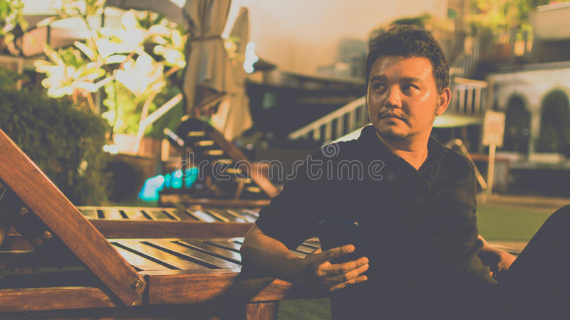 Asien-Mann denken mit Smartphone am Poolside lizenzfreie stockbilder