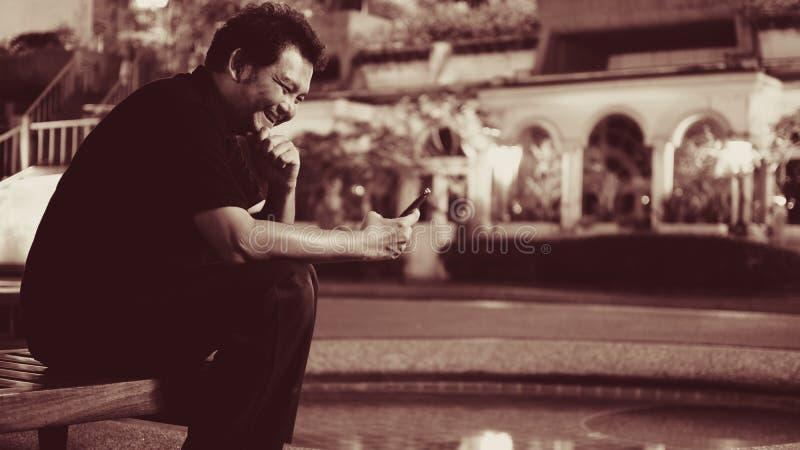Asien-Mann, der unter Verwendung des Smartphone über Poolside lacht lizenzfreie stockbilder