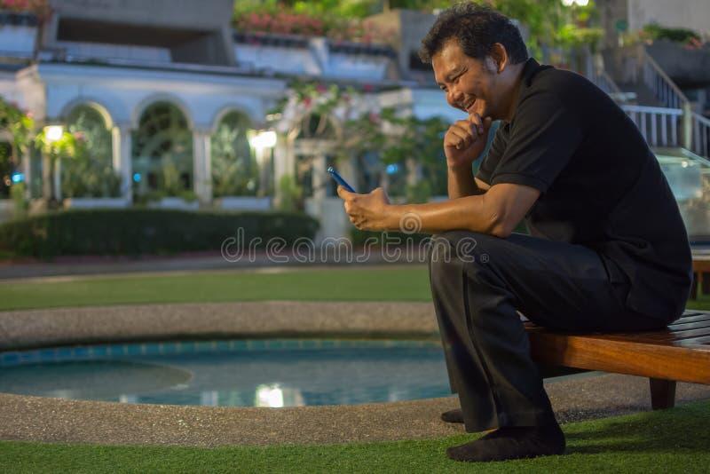 Asien-Mann, der unter Verwendung des Smartphone über Poolside lacht stockfotos