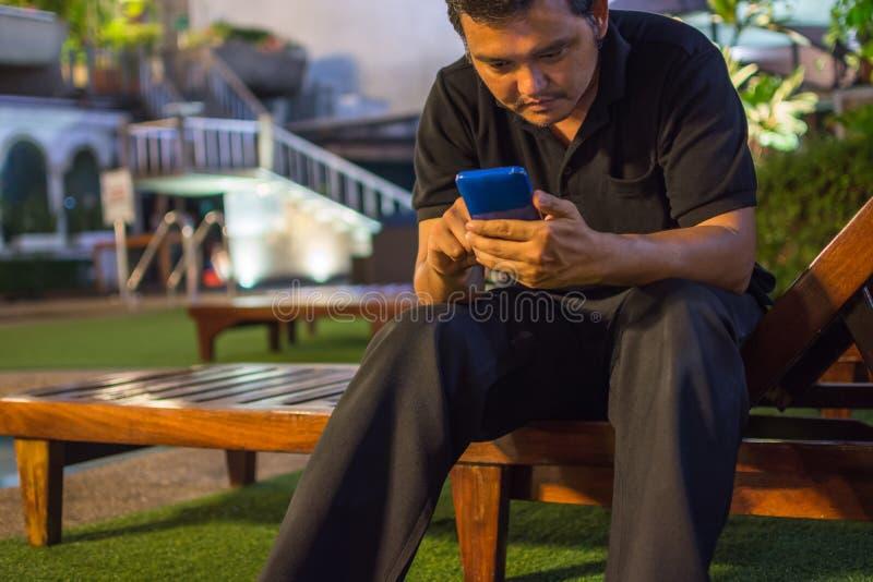 Asien-Mann, der unter Verwendung des Smartphone am Poolside lächelt lizenzfreie stockbilder
