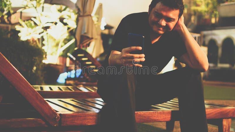 Asien-Mann, der unter Verwendung des Smartphone am Poolside lächelt stockfoto