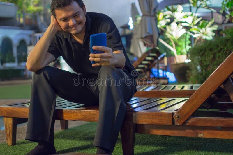 Asien-Mann, der unter Verwendung des Smartphone am Poolside lächelt lizenzfreie stockfotografie