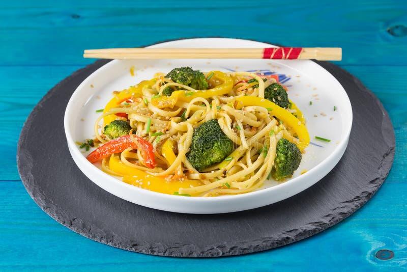 Asien mat Rör småfiskudonnudlar med grönsaker på en vit platta, blå träbackgound som in lagas mat, wokar arkivfoto