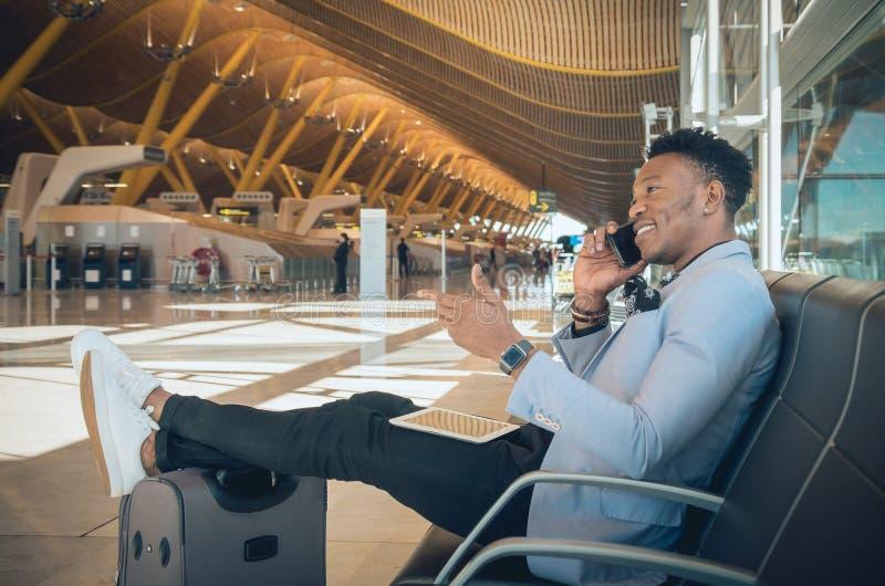 Asientan al hombre de negocios joven en el aeropuerto que sonríe y que habla b imagenes de archivo