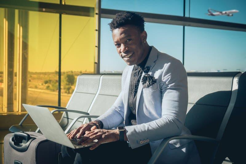 Asientan al hombre de negocios joven en el aeropuerto que trabaja con un ordenador portátil imagen de archivo libre de regalías