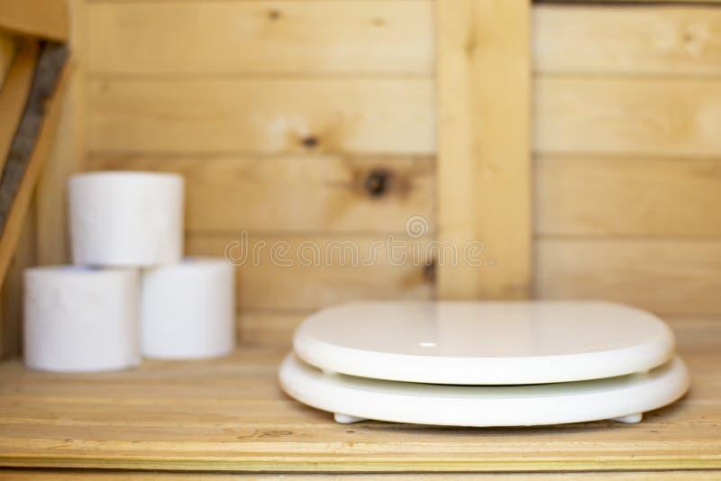 Asiento de inodoro moderno del color blanco en un WC rústico, de madera del lavabo, en los rollos del fondo del papel imágenes de archivo libres de regalías