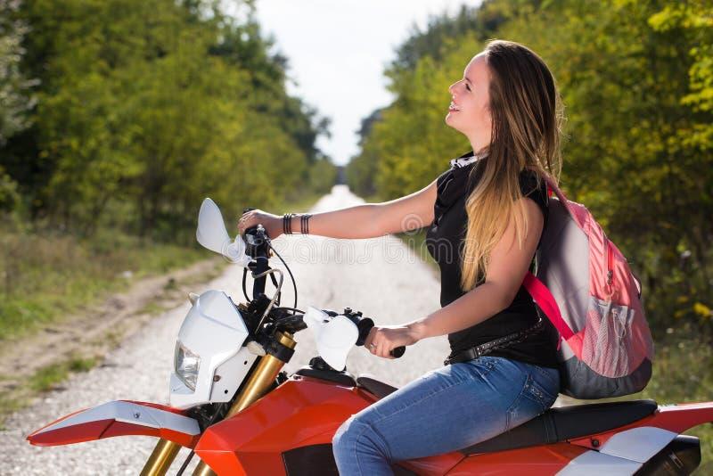 Asiento de la mujer joven en la motocicleta imagen de archivo libre de regalías