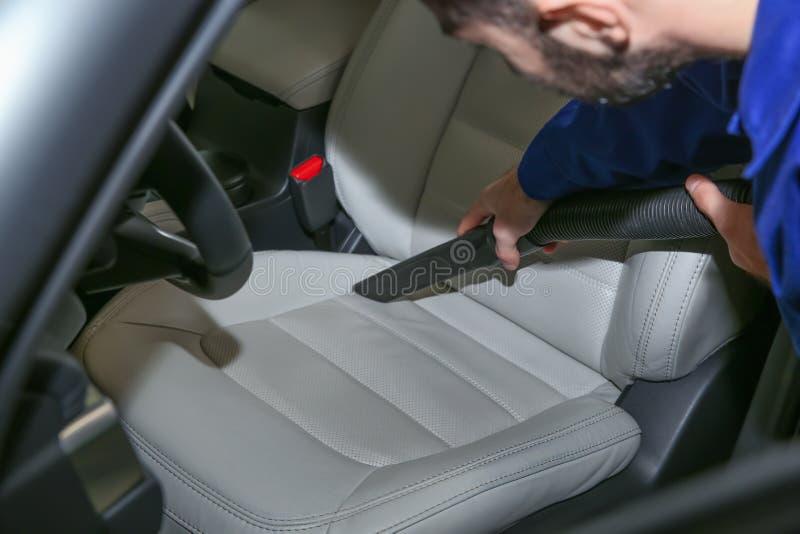 Asiento del automóvil del trabajador que limpia con la aspiradora Servicio de la colada de coche foto de archivo libre de regalías