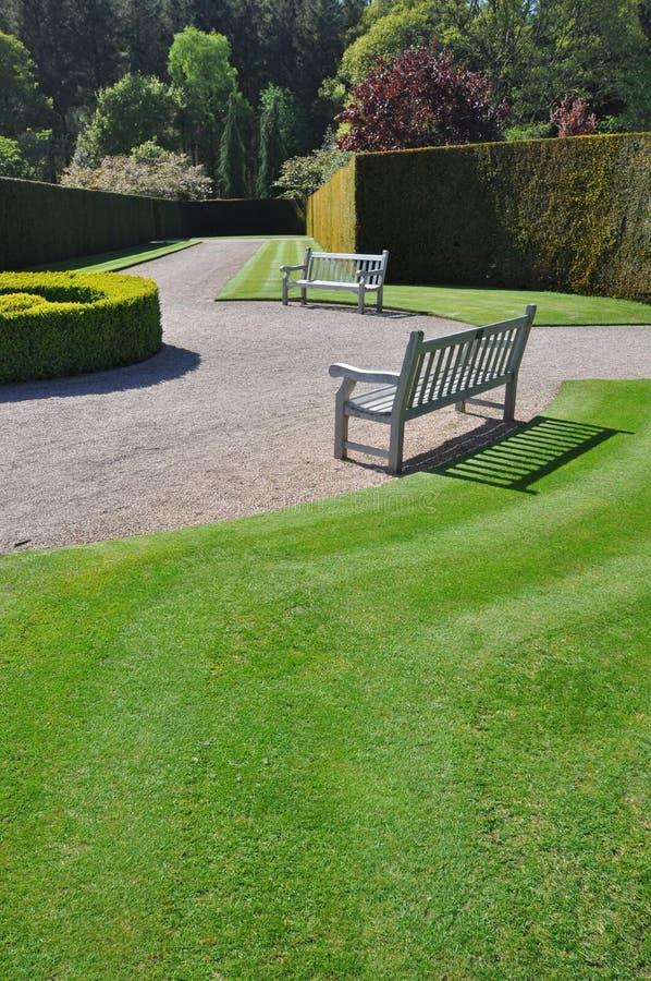 Asiento en un jardín inglés formal foto de archivo
