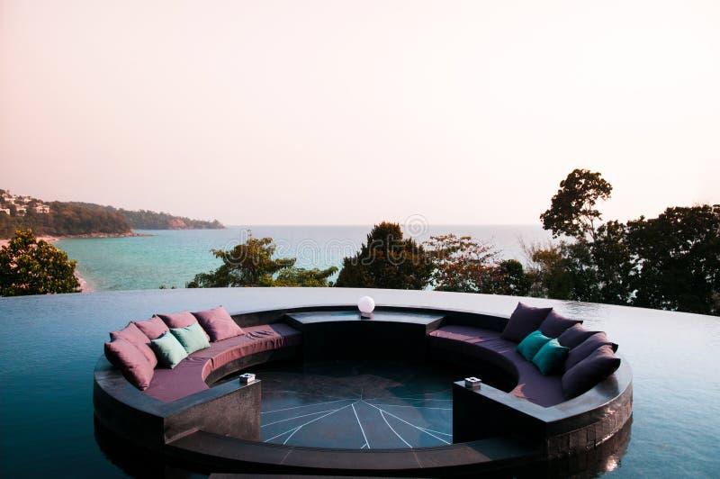 Asiento hundido en la piscina del borde del infinito con vista al mar adentro incluso imagen de archivo libre de regalías