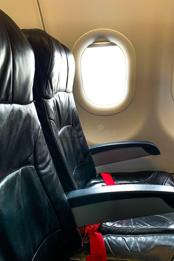 Asiento negro del aeroplano cinturón y ventana rojos de seguridad en la clase de economía de la cabina imagen de archivo libre de regalías