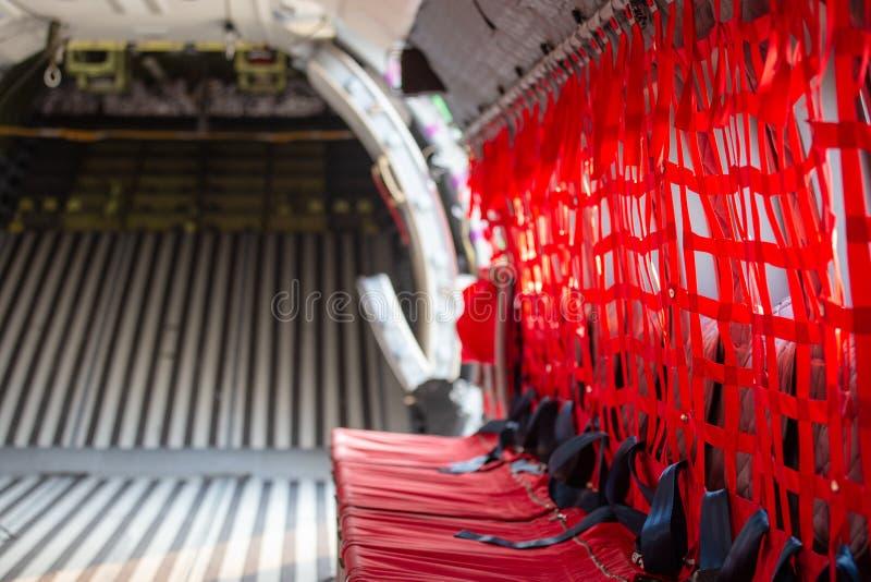 Asiento rojo con el cinturón de seguridad para las fuerzas del paracaidista o del airborn en mili fotografía de archivo