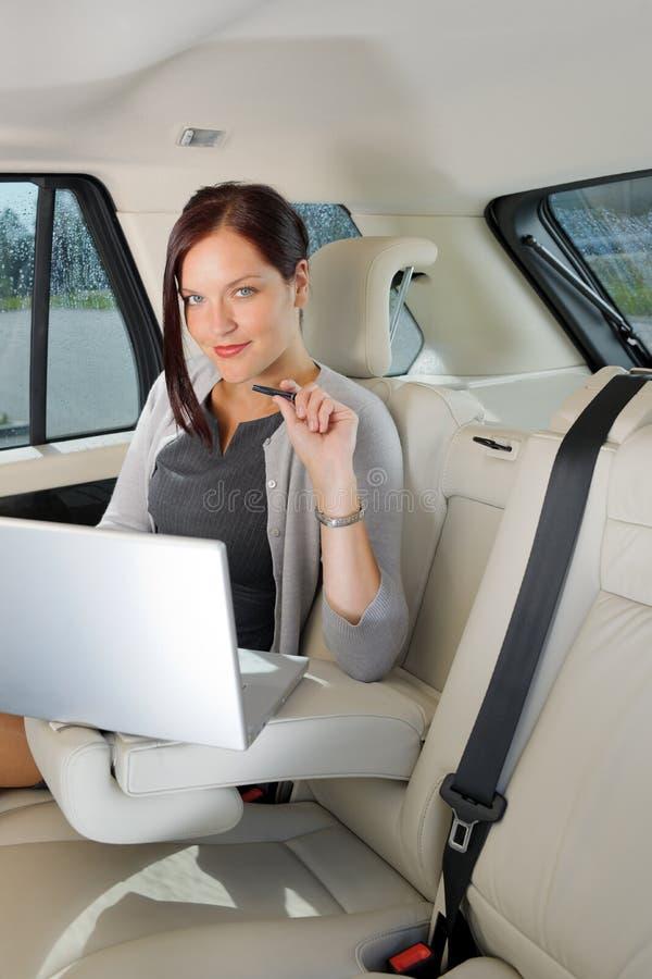 Asiento trasero ejecutivo del coche de la computadora portátil del trabajo de la empresaria