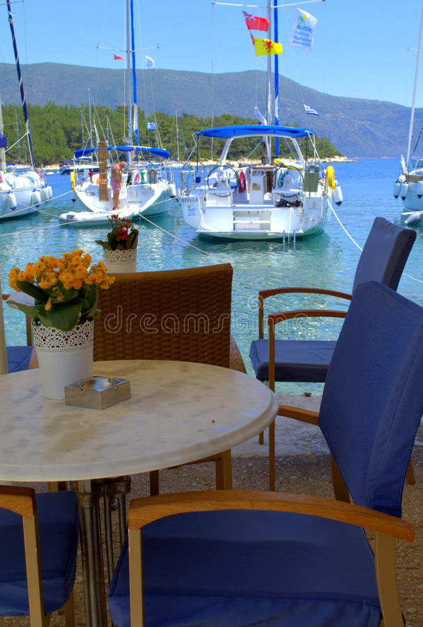 Asiento y barcos del restaurante en agua de mar azul imagenes de archivo