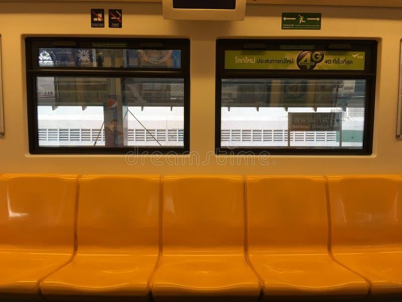 Asientos amarillos en skytrain para en la estación de destino imagenes de archivo