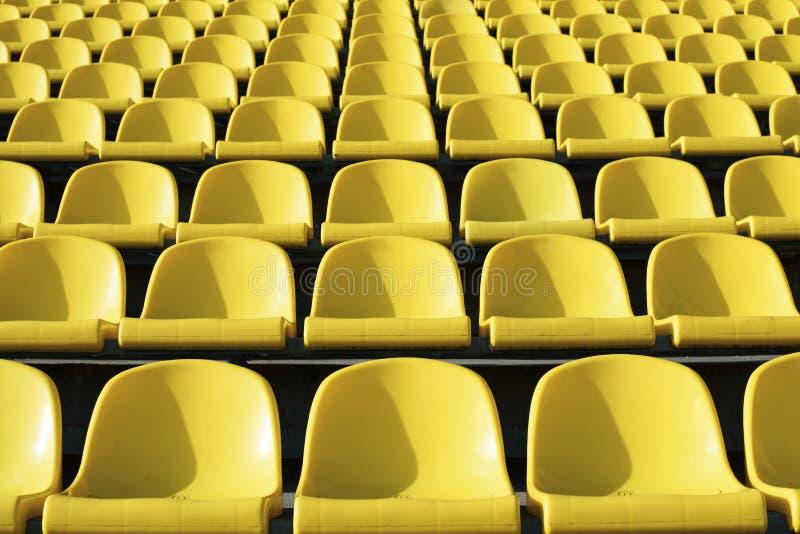 Asientos amarillos plásticos vacíos en el estadio, arena deportiva de la puerta abierta fotografía de archivo