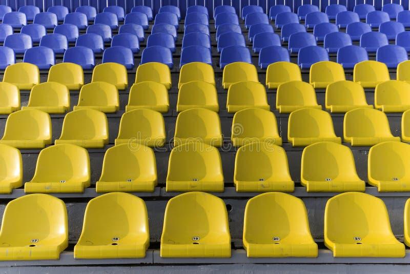 Asientos amarillos y azules del estadio fotos de archivo