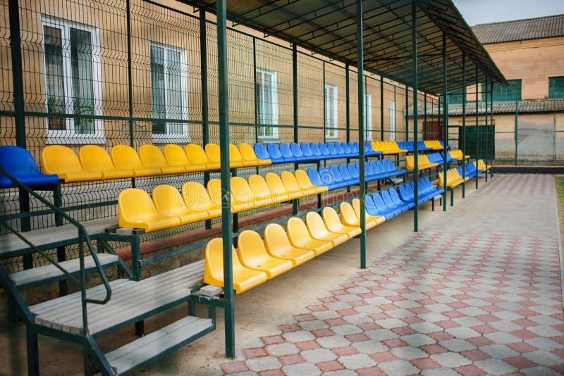 Asientos azules y amarillos vacíos de los deportes del soporte magnífico en el patio trasero de la escuela en el estadio fotos de archivo libres de regalías