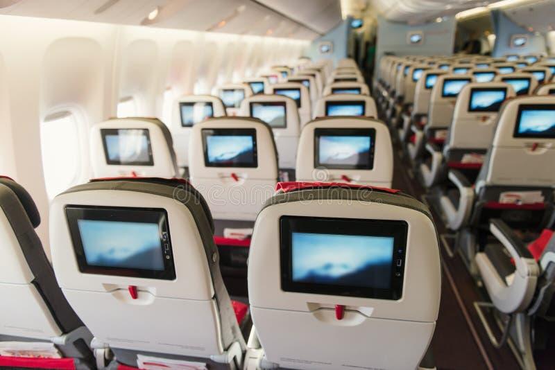 Asientos a bordo del aeroplano Clase de economía con las pantallas imagen de archivo libre de regalías