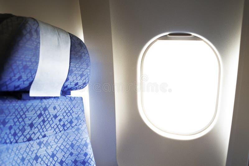 Asientos cómodos de los aviones con el reposacabezas por la ventana foto de archivo