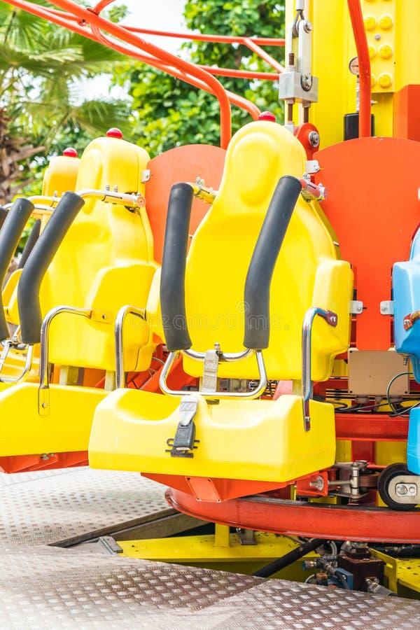 Asientos coloridos de la montaña rusa en el parque de atracciones fotografía de archivo