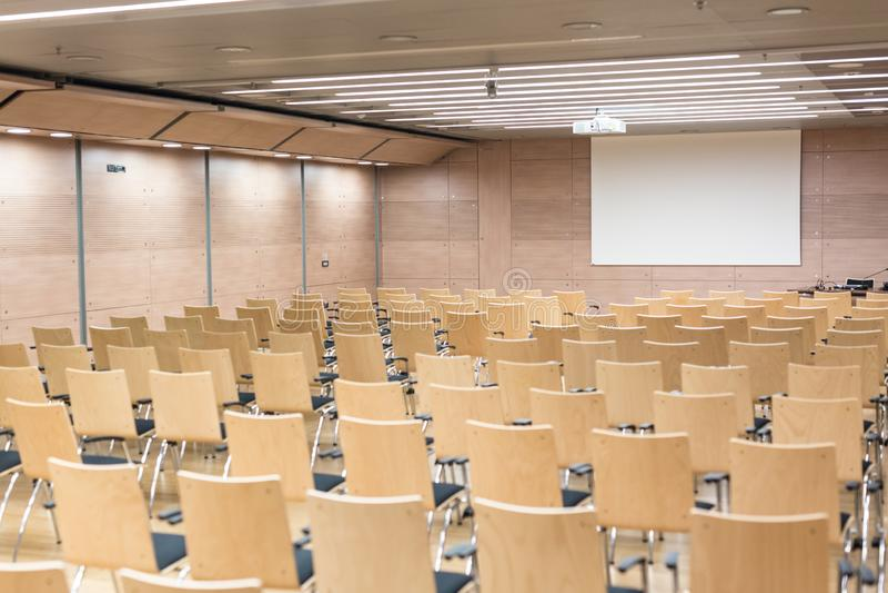 Asientos de madera vacíos en una sala de conferencias cotmporary foto de archivo