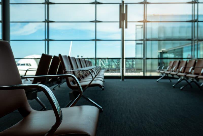 Asientos de pasajero en salón de la salida en el terminal de aeropuerto Interior del terminal de aeropuerto Sillas en área de la  imagen de archivo libre de regalías
