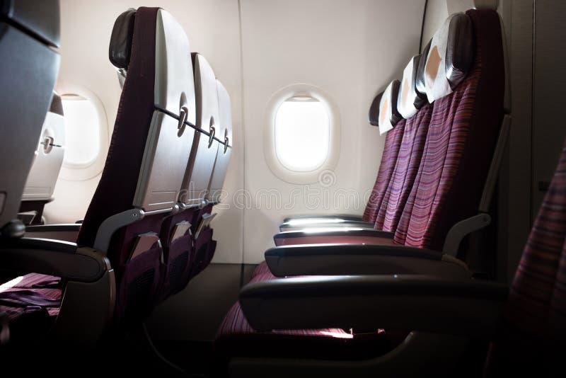 Asientos del aeroplano en la cabina con la ventana por la mañana imagen de archivo