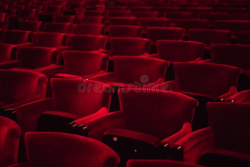Asientos del paño rojo en un pasillo vacío del cine imagen de archivo libre de regalías