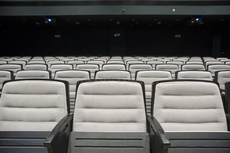 Asientos grises vacíos en teatro o conferencia fotos de archivo